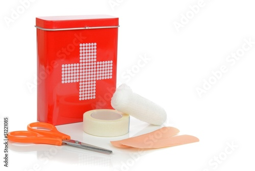 A travel first aid kit tin with contents on a white background