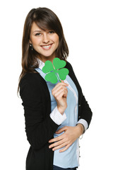 Smiling young woman holding shamrock leaf