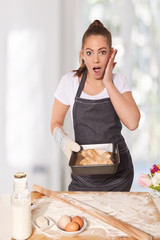 Baking woman surprised by perfect bread rolls