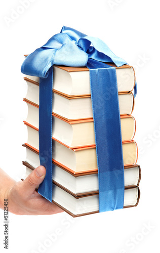 Book as a gift. A stack of books in female hand on a white backg
