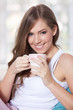 Portrait of a beautiful young woman holding a cup of hot drink