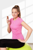 Young beautiful woman eating chocolate during workout
