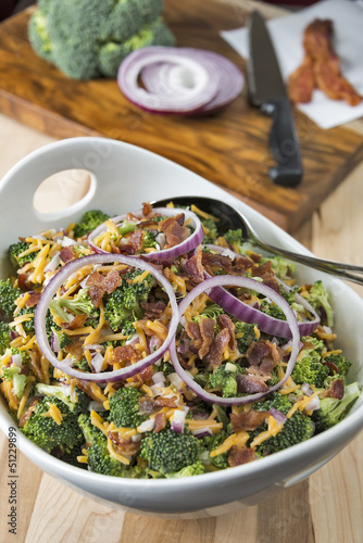 Bowl of broccoli salad with ingredients