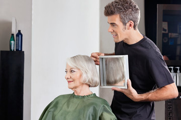 Hairstylist Showing Finished Haircut To Customer At Parlor