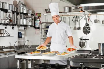 Confident Chef Presenting Pasta Dishes