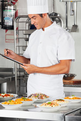 Male Chef With Clipboard Checking List Of Pastas