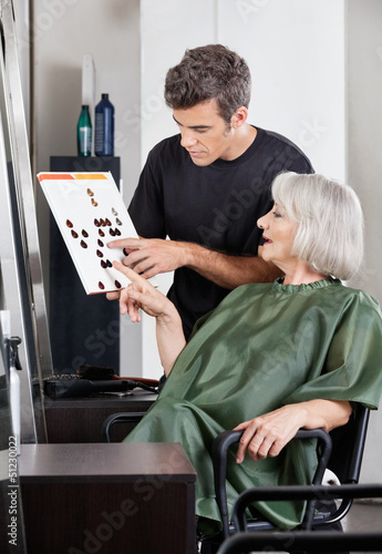 Hairdresser Advising Female Client In Selecting Color
