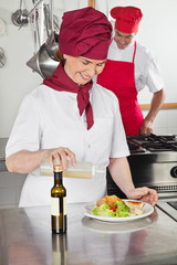 Female Chef Pouring Oil On Dish