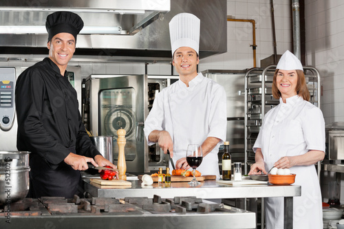 Chefs Working In Industrial Kitchen