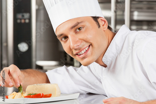 Happy Male Chef Garnishing Dish