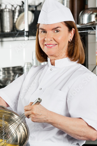 Chef Mixing Egg With Wire Whisk In Bowl