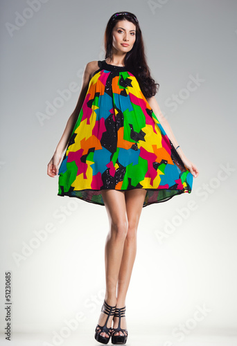 sexy woman wearing colorful summer dress on light grey