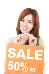 happy  woman showing shopping bag with sale written