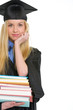 Young woman in graduation gown with stack of books