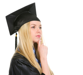Thoughtful young woman in graduation gown looking on copy space