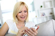 Smiling young woman at home using smartphone
