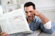 Man at home reading bad news on newspaper