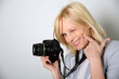 Cheerful woman photographer holding camera