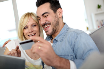 Cheerful couple at home doing online shopping