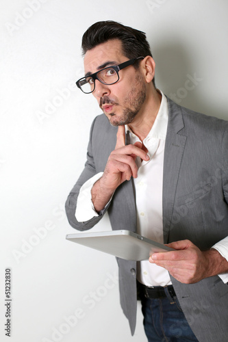 Man using tablet with questioning look