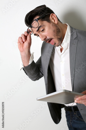 Man looking at tablet with surprised look