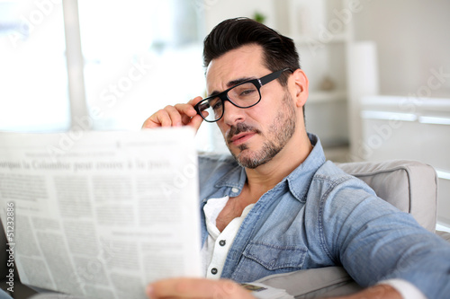 Cheerful guy reading newspaper in sofa
