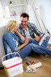 Couple sitting on the floor choosing paint colour