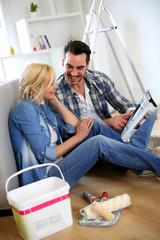 Couple sitting on the floor choosing paint colour