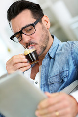 Man with glasses drinking coffee and using tablet