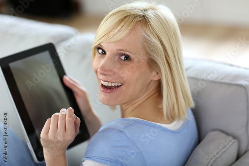 Smiling woman using tablet in sofa