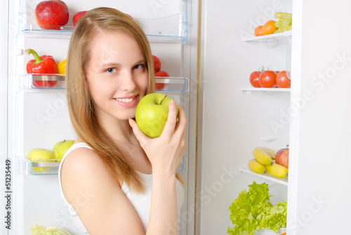 Beautiful smiling girl near the refrigerator