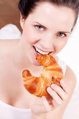 Junge hübsche brünette frau beiße in ein croissant
