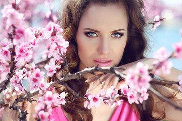 Stare. Outdoors portrait of beautiful woman model in pink blosso