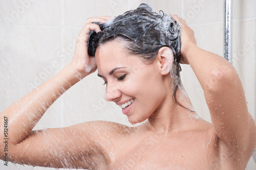 Young woman washing  head by shampoo