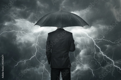 Businessman with umbrella standing in the rain