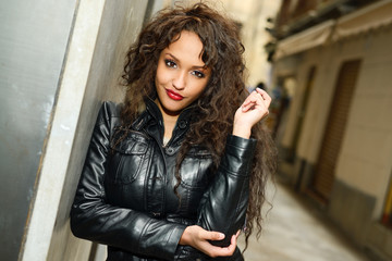 Attractive black woman in urban background wearing leather jacke