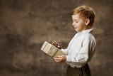 Child holding gift box. Vintage style.