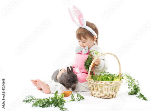 Child in bunny hare costume holding rabbit and carrot.
