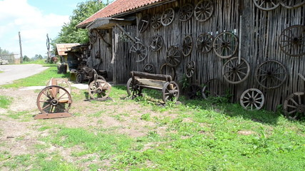 retro carriage cart wheels hang on rural building wall bench