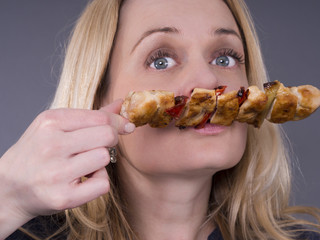 Hungry woman enjoying smell of grilled meat