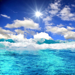 Meer mit Wellen, Sonne, blauem Himmel und Wolken