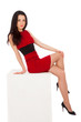 beautiful thin brunette woman in red dress sitting on cube