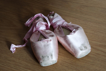 Detail of pointe shoes on wooden floor
