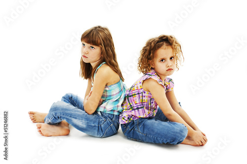 Two little girls back to back in quarrel