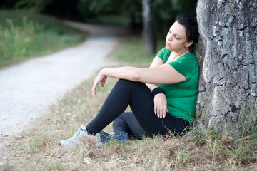Tired overweight woman sitting by the tree after training