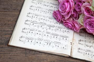 alte Musiknoten mit rosa Rosen