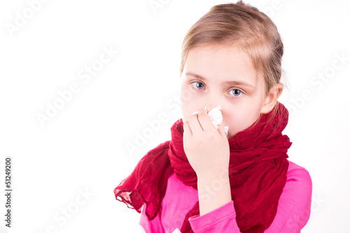 Sick little girl sneezing with napkin