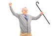 A happy senior man holding a cane and gesturing happiness