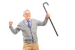 A senior man holding a cane and gesturing happiness, looking at