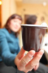 woman's hand with plastic cup of coffee